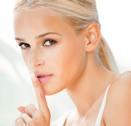 retrato de la mujer rubia hermosa con el dedo en los labios