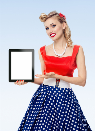 Woman, showing blank no-name tablet pc monitor, with copyspace, dressed in pin-up style dress in polka dot, on blue background. Caucasian blond model posing in retro fashion vintage shoot.