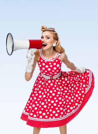Portrait of woman holding megaphone, dressed in pin-up style red dress in polka dot and white gloves, on blue background. Caucasian blond model posing in retro fashion vintage studio shoot.
