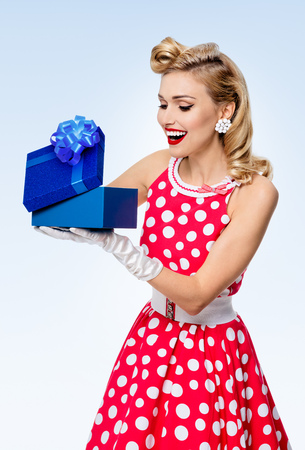 Portrait of beautiful young happy woman dressed in pin-up style red dress in polka dot and white gloves, on blue background. Caucasian blond model posing in retro fashion studio shoot.