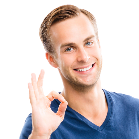 Portrait of cheerful young man showing okay gesture, isolated over white background. Emotions and success concept. Stock Photo