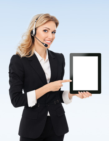 Portrait of support phone operator in headset showing blank no-name tablet pc monitor, with copyspace area for text or slogan, on blue background. Success in business, job and education concept.