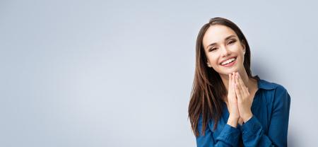 Retrato de feliz gesuring joven sonriente en ropa azul elegante casual, sobre fondo gris, con el área de copyspace para advertisiment, texto o lema. Concepto de publicidad. Composición de banner horizontal. Foto de archivo