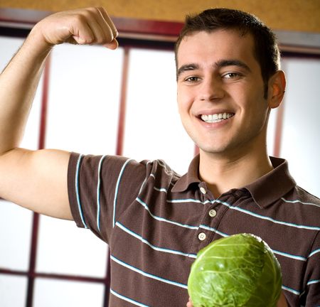 Portrait of cheerful happy smiling man with cabbage, showing biceps. Healthy eating concept. Stock Photo