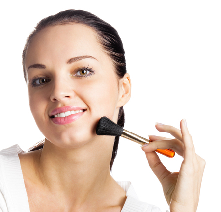 Young happy smiling woman with cosmetics brush, isolated over white background Stock Photo