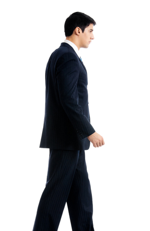 Full body portrait of walking young businessman, isolated over white background. Success in business and education concept. photo