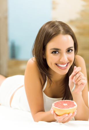 Portrait of young happy smiling woman eating grapefruit at home. Dieting and healthy eating concept. photo