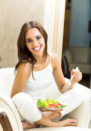 Young happy smiling woman with fegetarian salad at home. Dieting and healthy eating concept. photo