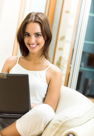 Young happy beautiful smiling woman working with laptop, at home photo