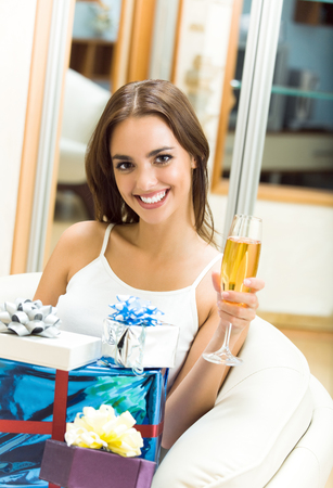 Portrait of young happy smiling woman with champagne and gifts at home photo