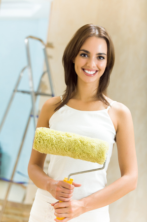 Young happy smiling beautiful woman with paint roller in new house