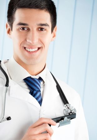 medical laboratory: Happy doctor with clipboard at office. Medicare, health care and medical occupation concept shot.