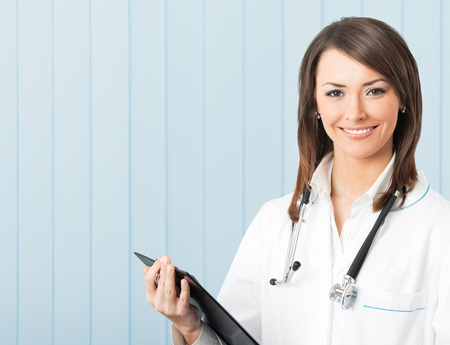 Portrait of happy young smiling female doctor with clipboard at office. Medicare, health care and medical occupation concept shot.