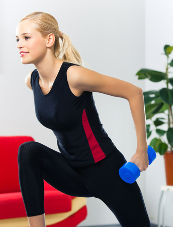Portrait of young happy smiling woman in sportswear, doing fitness exercise with dumbbell, at home. Health lifestyle, weight lossing and workout concept shot. photo