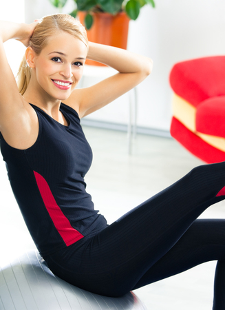 Portrait of young happy smiling woman in sportswear, doing fitness exercise with fit ball, at home. Health lifestyle, weight lossing and workout concept shot. photo