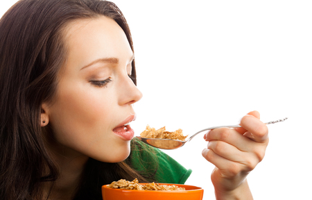 Portrait of young smiling woman eating muesli or corn flakes, isolated over white background. Healthy eating and weight lossing concept shot.