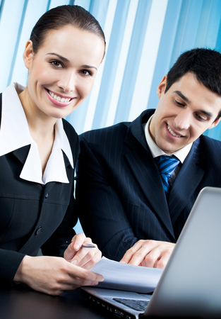 Two happy businesspeople working together at office. Teamwork, partnership and success in business. Stock Photo