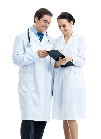 Full body portrait of two happy smiling young medical people with clipboard, isolated over white background. Medicare, health care and medical occupation concept shot. photo