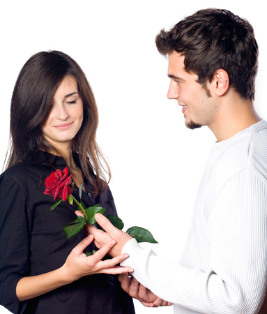 Young happy smiling couple with rose, isolated over white background. Love, relationships and dating concept. Stock Photo