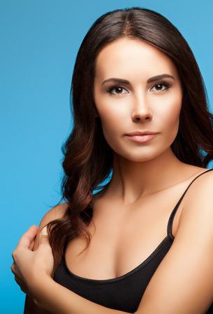 portrait of beautiful brunette woman, on blue background