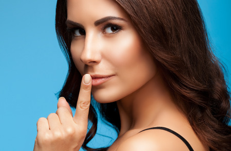 portrait of beautiful young brunette woman with finger on lips, on blue background Stock Photo