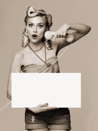 sign: Portrait of beautiful young woman with phone and blank signboard, dressed in pin-up style. Caucasian blond model posing in retro fashion and vintage concept. Black and white. Stock Photo