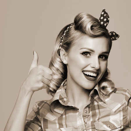 Portrait of beautiful young happy smiling woman, showing thumb up gesture, dressed in pin-up style. Caucasian blond model posing in retro fashion and vintage concept. Black and white.