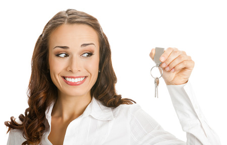 give out: Portrait of young happy smiling businesswoman or real estate agent showing keys from new house, isolated on white background. Success in business concept.