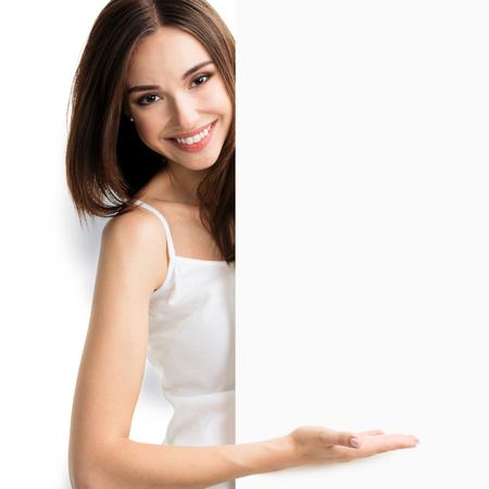 eslogan: Retrato de mujer joven y sonriente en la camiseta blanca ropa informal elegante, mostrando cartel en blanco vacío con área de copyspace de texto o lema, aislado contra el fondo blanco