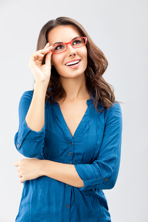 Portrait of happy smiling young cheerful businesswoman, in glasses, looking up, over grey background. Caucasian brunette model in business concept studio shoot. Square composition. photo