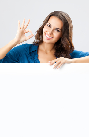 Happy smiling beautiful young businesswoman showing blank signboard with empty copyspace area for slogan or advertising text message, on grey background. photo