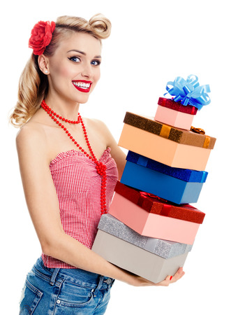 Portrait of beautiful young happy smiling woman in pin-up style clothing, holding gift boxes, isolated over white background. Caucasian blond model posing in retro fashion and vintage concept shoot. Stock Photo