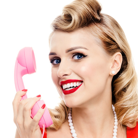 Portrait of beautiful woman with phone dressed in pin-up style, isolated over white background. Caucasian blond model posing in retro fashion and vintage concept studio shoot. Stock Photo