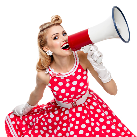 grooming: Portrait of woman holding megaphone, dressed in pin-up style red dress in polka dot and gloves, isolated on white background. Caucasian blond model posing in retro fashion vintage shoot. Square composition.