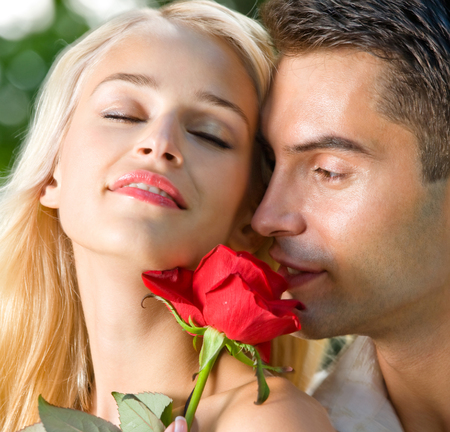 Young happy amorous cheerful couple with rose, outdoor. Love, relationships and dating concept. photo