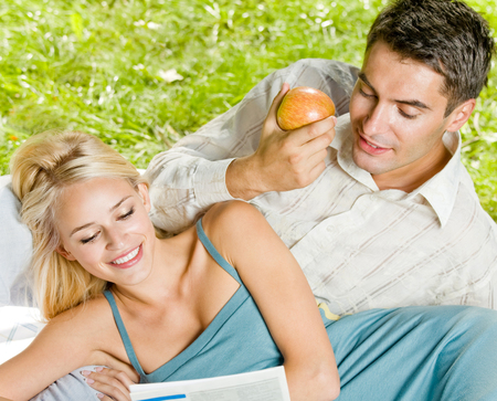 Young happy smiling cheerful couple reading together newspaper, outdoor. Love, relationships and dating concept. photo