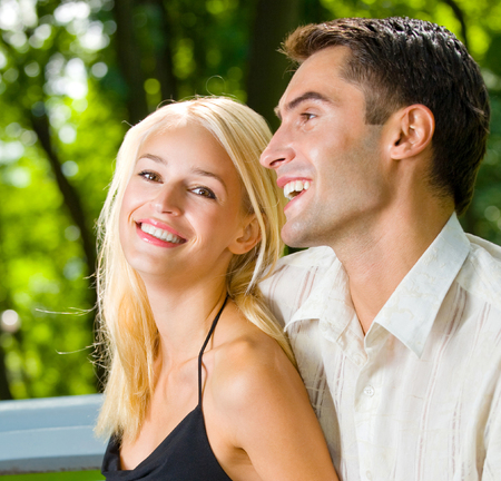 Portrait of young happy smiling cheerful attractive couple together, outdoors. Love, relationships and dating concept. photo