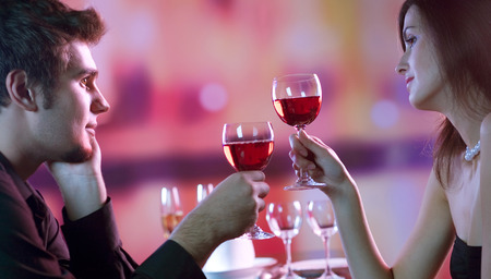 Young happy amorous couple with glasses of redwine on romantic date at restaurant. Love, relationships and dating concept. Imagens