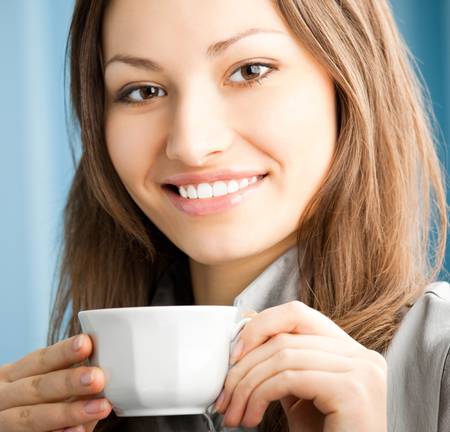 Cheerful smiling businesswoman drinking coffee at office. Success in business and people at work concept. Stock Photo