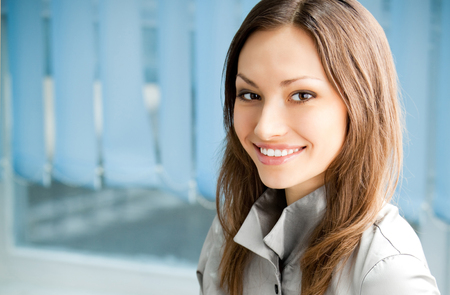 Young happy smiling cheerful businesswoman at office, with copyspace. Success in business and people at work concept. photo