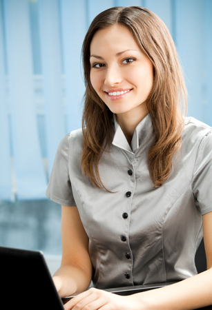 Young cheerful smiling businesswoman working with laptop at office. Success in business and people at work concept. photo