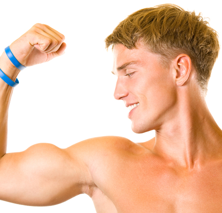 Portrait of happy smiling muscular young man showing biceps, isolated on white background