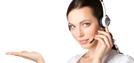Portrait of happy smiling cheerful customer support phone operator in headset showing something or copyspace area for text, isolated over white background. Caucasian brunette model in help service and client consulting call center concept.