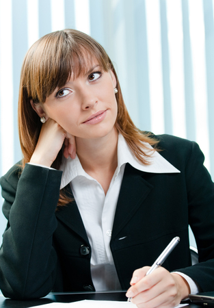 Young thinking business woman writing at office. Business organization and education concept.