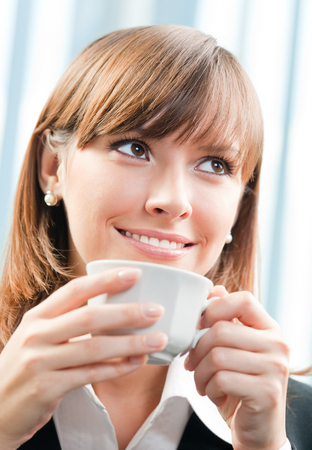 Cheerful smiling businesswoman drinking coffee at office. Success in business, job and education concept shot. photo