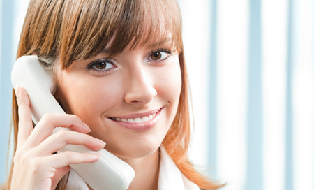 Young cheerful businesswoman with phone at office. Help service, client consulting and call center concept. photo