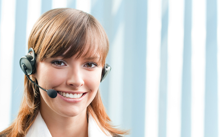 Young cheerful smiling support phone female operator in headset at office, with copyspace. Help service, client consulting and call center concept. photo