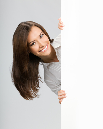 Happy smiling young businesswoman showing blank area for sign or copyspase, against grey background. PR and advertisiment business concept.