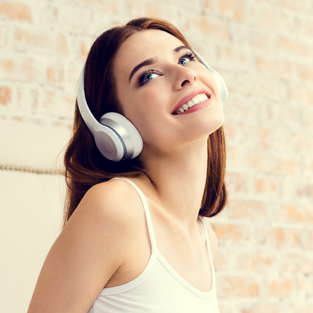 audio book: Happy young woman listening headphones at home, bedroom. Caucasian beautiful brunette model in technology and leisure concept shoot.