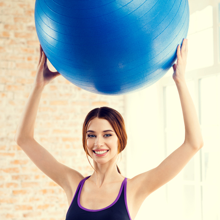 fitball: Portrait of young happy smiling woman in sportswear, doing fitness exercise with fit ball, at home. Health lifestyle, weight lossing and workout concept shot.